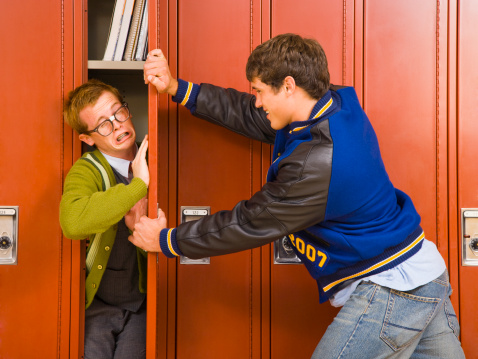 High school jock pushing nerd in locker